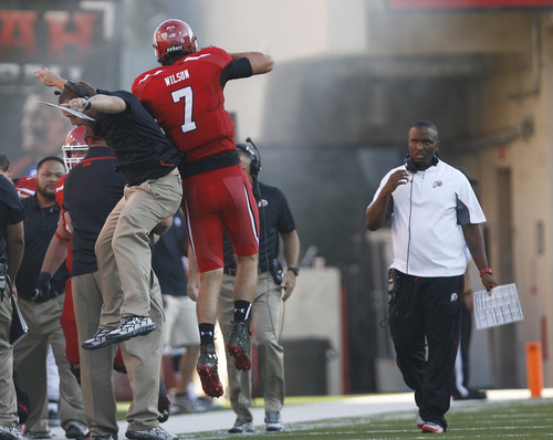 Scott Sommerdorf   |  The Salt Lake Tribune Utah QB Travis Wilson jumps up with a coach on the sidelines after his 3 yard TD pass to Dres Anderson as took a quick 7-0 lead over USU early in the 1st period, Thursday, August 29, 2013. Utah co-OC brian Johnson is at right.