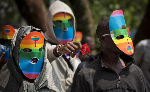 FILE - In this Monday, Feb. 10, 2014 file photo, Kenyan gays and lesbians and others supporting their cause wear masks to preserve their anonymity and one holds out a condom, as they stage a rare protest, against Uganda's increasingly tough stance against homosexuality and in solidarity with their counterparts there, outside the Uganda High Commission in Nairobi, Kenya. Uganda's President Yoweri Museveni is expected to sign Monday, Feb. 24, 2014 a controversial anti-gay bill that allows harsh penalties for homosexual offenses, a bill which rights groups have condemned as draconian in a country where homosexuality is already illegal. (AP Photo/Ben Curtis, File)