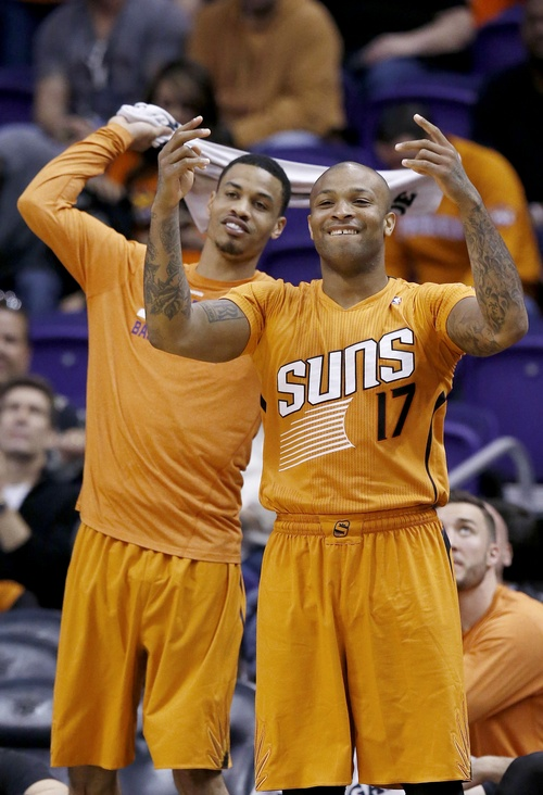 Phoenix Suns' P.J. Tucker (17) and Gerald Green cheer on their teammates during the second half of an NBA basketball game against the San Antonio Spurs, Friday, Feb. 21, 2014, in Phoenix. The Suns defeated the Spurs 106-85. (AP Photo/Ross D. Franklin)