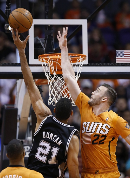 San Antonio Spurs' Tim Duncan (21) gets off a shot over Phoenix Suns' Miles Plumlee (22) during the first half of an NBA basketball game, Friday, Feb. 21, 2014, in Phoenix. (AP Photo/Ross D. Franklin)