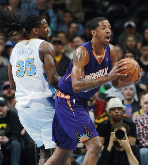 Phoenix Suns forward Channing Frye, front, pulls in loose ball in front of Denver Nuggets forward Kenneth Faried during the first quarter of an NBA basketball game in Denver on Tuesday, Feb. 18, 2014. (AP Photo/David Zalubowski)