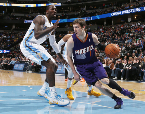 Phoenix Suns guard Goran Dragic, of Slovenia, drives the lane for a shot as Denver Nuggets center J.J. Hickson, left, and guard Randy Foye defend during the first quarter of an NBA basketball game in Denver on Tuesday, Feb. 18, 2014. (AP Photo/David Zalubowski)