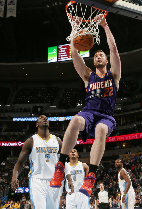 Phoenix Suns center Miles Plumlee, front, hangs from rim after dunking, while Denver Nuggets center J.J. Hickson watches during the first quarter of an NBA basketball game in Denver on Tuesday, Feb. 18, 2014. (AP Photo/David Zalubowski)