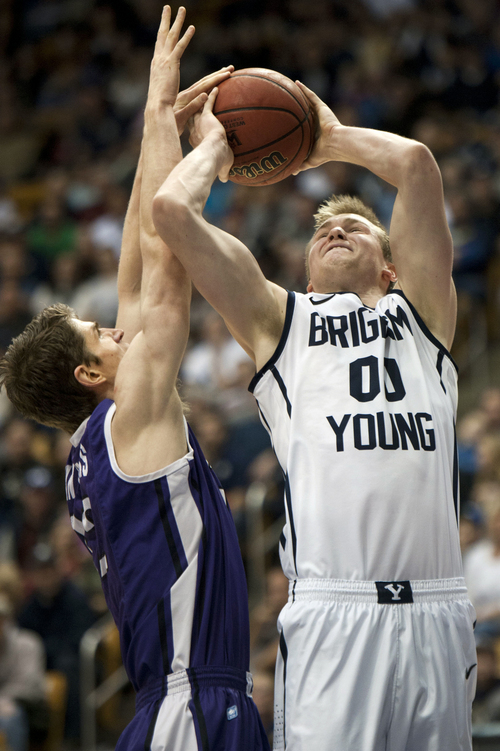 BYU's Eric Mika shoots as Portland's Thomas van der Mars, left, defends during the first half of an NCAA college basketball game in Provo, Utah, Saturday, Feb. 22, 2014. (AP Photo/The Daily Herald, Grant Hindsley)