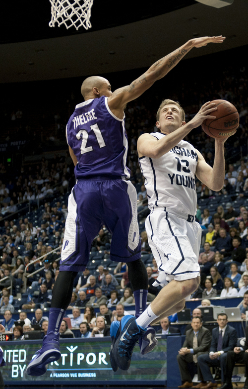 Portland's Korey Thieleke blocks BYU's Josh Sharp during the second half of an NCAA college basketball game in Provo, Utah, Saturday, Feb. 22, 2014. (AP Photo/The Daily Herald, Grant Hindsley)