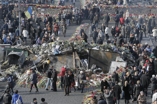 Flowers cover the ground and barricades where protesters were killed in a recent clash with riot police in Kiev's Independence Square, Ukraine, Wednesday, Feb. 26, 2014.  Ukraine has been consumed by a three-month-long political crisis. President Viktor Yanukovych and protest leaders signed an agreement last week to end the conflict that left more than 80 people dead in just a few days in Kiev. Shortly after, Yanukovych fled the capital for his power base in eastern Ukraine but his exact whereabouts are unknown.  (AP Photo/Efrem Lukatsky)