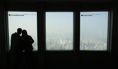 A couple watches the Seoul skyline covered with a thick haze at Seoul Tower's observation deck in Seoul, South Korea, Wednesday, Feb. 26, 2014. The Seoul metropolitan government issued a dust warning, urging people to stay indoors. ( AP Photo/Ahn Young-joon)