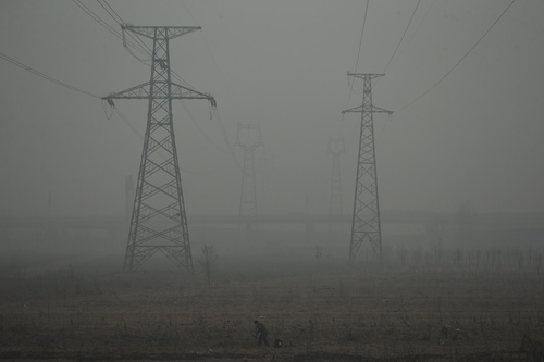 A farmer shovels in a field near electric pylons in heavy haze on a severely polluted day in Shijiazhuang, in northern China's Hebei province, Wednesday, Feb. 26, 2014. (AP Photo/Alexander F. Yuan)