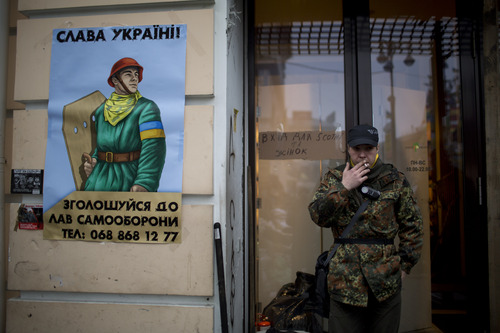 """An anti-Yanukovych protester stands guard outside a building that was turned into a base for a self-defense unit in Kiev's Independence Square, the epicenter of the country's current unrest, Ukraine, Wednesday, Feb. 26, 2014. Ukraine has been consumed by a three-month-long political crisis. President Viktor Yanukovych and protest leaders signed an agreement last week to end the conflict that left more than 80 people dead in just a few days in Kiev. Shortly after, Yanukovych fled the capital for his power base in eastern Ukraine but his exact whereabouts are unknown. The poster in the left side reads in Ukrainian: """"Glory to Ukraine. Sign up to join us for the defense unit"""". (AP Photo/Emilio Morenatti)"""