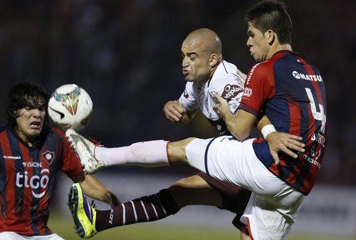 Danilo Ortiz of Paraguay's Cerro Porteno, right, fights for the ball with Santiago Silva of Argentina's Lanus, during a Copa Libertadores game in Asuncion, Paraguay, Wednesday, Feb. 26, 2014. (AP Photo/Jorge Saenz)