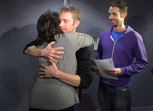 Scott Sommerdorf   |  The Salt Lake Tribune Seth Anderson, center, hugs a friend after he and Michael Ferguson, right,  were the first couple married under the now legal same sex marriage decision handed down by a federal judge just minutes before their ceremony at the Salt Lake County offices, Friday December 20, 2013.