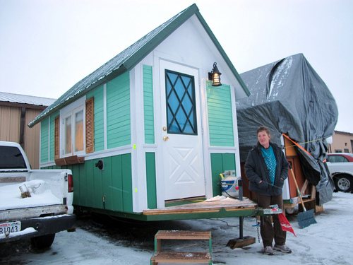 In this Jan. 16, 2014 photo Betty Ybarra, 48, stands outside a tiny houses she and her boyfriend live in, in Madison, Wis. It is the first house built by OM Build, which wants to build nine houses in Madison for the homeless. (AP Photo/Carrie Antlfinger)