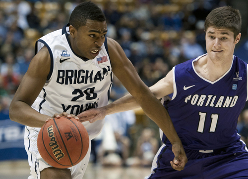 BYU's Anson Winder charges past Portland's Bobby Sharp (11) during the second half of an NCAA college basketball game in Provo, Utah, Saturday, Feb. 22, 2014. (AP Photo/The Daily Herald, Grant Hindsley)
