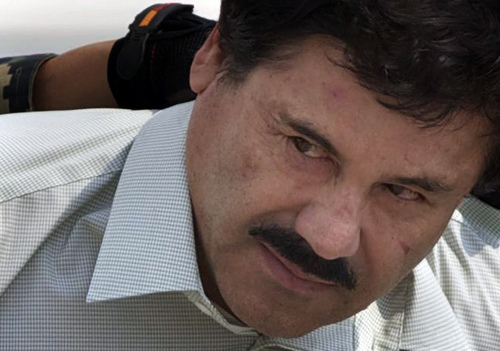"""ADVANCE FOR USE SUNDAY, MARCH 2 - FILE - In this Feb. 22, 2014, file photo, Joaquin """"El Chapo"""" Guzman, in handcuffs, is escorted to a helicopter by Mexican navy marines in Mexico City, Mexico. At least seven U.S. courts have indictments pending against him, and several are pressing for extradition. In Mexico, he faces organized-crime charges in four Mexican states and in Mexico City. He could, barring another escape, spend the rest of his life behind bars. (AP Photo/Dario Lopez-Mills, File)"""
