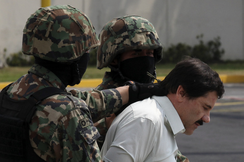 "ADVANCE FOR USE SUNDAY, MARCH 2 - FILE - In this Feb. 22, 2014, file photo, Joaquin ""El Chapo"" Guzman, in handcuffs, is escorted to a helicopter by Mexican navy marines in Mexico City, Mexico. At least seven U.S. courts have indictments pending against him, and several are pressing for extradition. In Mexico, he faces organized-crime charges in four Mexican states and in Mexico City. He could, barring another escape, spend the rest of his life behind bars. (AP Photo/Dario Lopez-Mills)"