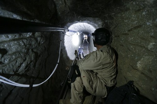 """ADVANCE FOR USE SUNDAY, MARCH 2 - In photo taken on Nov. 4, 2013, a Homeland Security Investigations member of the special response team looks south in a border tunnel equipped with lighting, ventilation and an electric rail system discovered between Tijuana, Mexico and San Diego in San Diego. Discovered on Oct. 30, 2013, the secret passage on the U.S.-Mexico border was linked by authorities to Mexico's Sinaloa cartel and its leader, Joaquin """"El Chapo"""" Guzman, who was arrested on Feb. 22, 2014 in Maztalan, Mexico. (AP Photo/Gregory Bull)"""