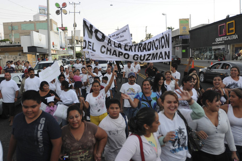 "ADVANCE FOR USE SUNDAY, MARCH 2 - FILE - In this Feb.  26, 2014 file photo, people march in support of jailed drug boss Joaquin Guzman, ""El Chapo"" in the city of Culiacan, Mexico. Hundreds of people marched on the streets of Culiacan, the drug lord's bastion, demanding that Guzman be freed. Guzman, the one they called shorty because of his 5'6 frame grew up poor and had no formal education, would rise from a small-time Mexican marijuana producer to lead the world's most powerful drug cartel.   (AP Photo/El Debate de Culiacan, Jonathan Telles, File)"