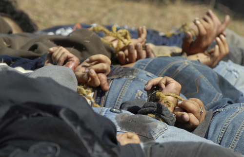"""ADVANCE FOR USE SUNDAY, MARCH 2 - FILE - In this Dec. 4, 2008, file photo, bodies from a total of 13 bullet-ridden men, with their hands tied behind their backs, victims of the drug war involving Joaquin """"El Chapo"""" Guzman's Sinaloa cartel, lie in a field near the town of San Ignacio in the pacific state of Sinaloa, Mexico. Guzman and his cohorts waged an increasingly bloody war over the year with rival gangs. (AP Photo/File)"""