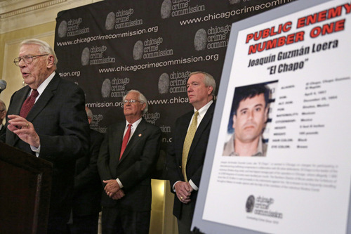 "ADVANCE FOR USE SUNDAY, MARCH 2 - FILE - In this Feb. 14, 2013. file photo, Art Bilek, executive vice president of the Chicago Crime Commission, left,  announces that Joaquin ""El Chapo"" Guzman has been named Chicago's Public Enemy No. 1, during a news conference in Chicago.  Guzman, the one they called ""shorty"" because of his 5'6"" frame, a man who grew up poor and had no formal education, would rise from a small-time Mexican marijuana producer to lead the world's most powerful drug cartel. (AP Photo/M. Spencer Green, File)"