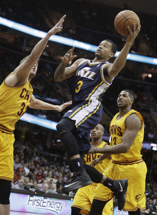 Utah Jazz's Trey Burke, center, shoots past Cleveland Cavaliers' Spencer Hawes, left, and Tristan Thompson (13), from Canada, during the first quarter of an NBA basketball game on Friday, Feb. 28, 2014, in Cleveland. (AP Photo/Tony Dejak)