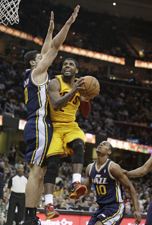 Cleveland Cavaliers' Kyrie Irving, center, jumps to the basket against Utah Jazz's Enes Kanter, left, from Turkey, and Alec Burks, right, during the third quarter of an NBA basketball game on Friday, Feb. 28, 2014, in Cleveland. (AP Photo/Tony Dejak)