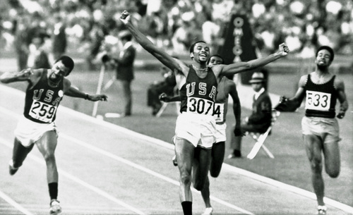 Tommie Smith of the U.S. raises his arms as he wins the 200 meters Olympic sprint in Mexico City Oct. 16, 1968.  Teammate John Carlos (259) finished third.  At far right is Michael Fray of Jamaica, who did not place.  Smith and Carlos caused controversy by raising black power salutes on the podium during their medal ceremony.  (AP Photo)