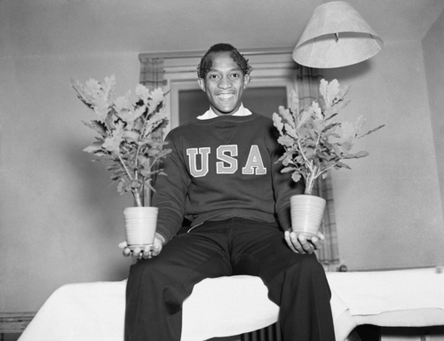 Happy over his double victory, Jesse Owens of Cleveland is shown with the Olympic Oaks in Berlin on August 8, 1936, given to each winner, which he won by capturing for the American first honors in the 100-meter dash and running broad jump. (AP Photo)