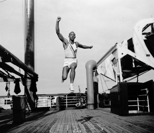 Jesse Owens, U.S. Olympic sprint and jumping star, takes a practice broad jump aboard the S.S. Manhattan at sea, while en route to Berlin, Germany, for the summer Olympics on July 27, 1936. (AP Photo/Joe Caneva)