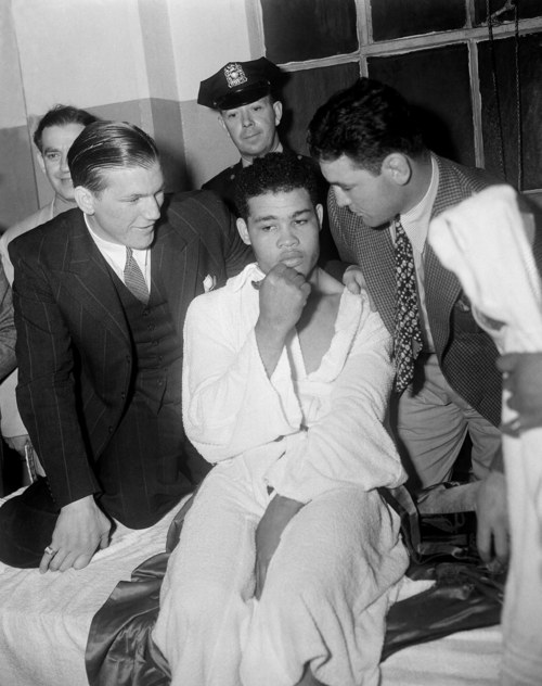 Well-wishers in Joe Louis dressing room after his speedy dispatch of Max Schmeling were two former adversaries--English Tommy Farr  of England, left,  who lasted the full 15 rounds in their bout in 1937, and Jim Braddock from whom Louis won the title by an eighth-round knockout in 1937.    Louis' face was unmarred by his encounter with the German challenger on this night,  June 23, 1938, at New York's Yankee Stadium.   This was the second meeting for Louis and Schmeling.   Louis the winner by a knockout, two minutes and four seconds into the first round.     (AP Photo)