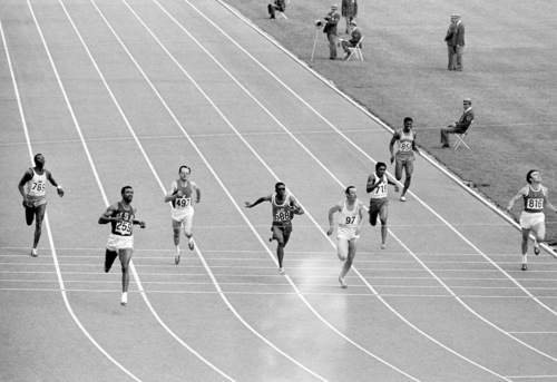 John Carlos (259) of the U.S. wins the opening heat in the 200-meter dash during the Summer Olympic Games in Mexico City, Mexico, Oct. 15, 1968.  Andres Calonce (97) of Argentina is second and Manikavas Legathesan (588) of Malaysia is third.  Other athletes follow in this order: Livio Berruti (497), Italy; Valentin Maslakov (816), Russia; Norman Chihota (769), Tanzania; Canagasabai Kunalan (719), Singapore; H.A. Hinds (858), Barbados.  (AP Photo)
