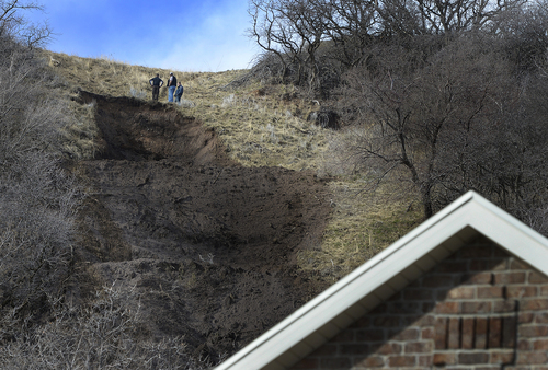 Scott Sommerdorf   |  The Salt Lake Tribune Men examine a mudslide on a hill behind homes on 1650 East in South Weber City that occurred after the hillside was weakened by overnight rains, seen Friday, Feb. 28, 2014. No homes below were damaged, but might be threatened by further rain. The same area was hit with a landslide in 2007 neighbors said.