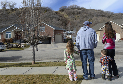 Scott Sommerdorf   |  The Salt Lake Tribune Neighbor Bryan Jenkins and family examine a mudslide on a hill behind homes on 1650 East in South Weber City that occurred after the hillside was weakened by overnight rains, seen Friday, Feb. 28, 2014. No homes below were damaged, but might be threatened by further rain. The same area was hit with a landslide in 2007 neighbors said.
