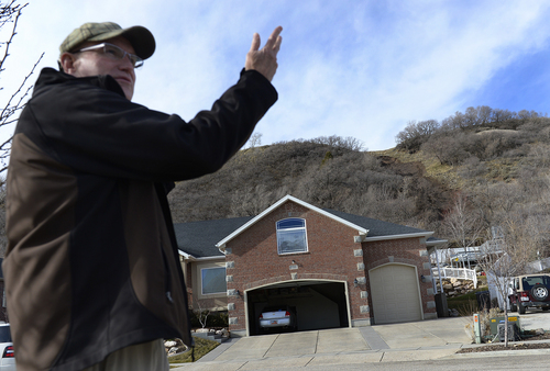 Scott Sommerdorf   |  The Salt Lake Tribune Homeowner Dave Hogan describes a mudslide on a hill behind his home on 1650 East in South Weber City as he talks with neighbors out looking at the damage. The slide occurred after the hillside was weakened by overnight rains, seen Friday, Feb. 28, 2014. No homes below were damaged, but might be threatened by further rain. The same area was hit with a landslide in 2007 neighbors said.