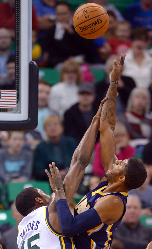 Steve Griffin  |  The Salt Lake Tribune   Utah Jazz power forward Derrick Favors (15) contests a shot from Indiana Pacers small forward Paul George (24) during first half action in the Utah Jazz versus Indiana Pacers at EnergySolutions Arena in Salt Lake City, Utah Wednesday, December 4, 2013.