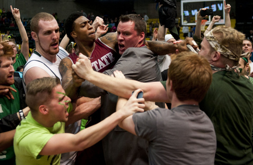 In this Thursday, Feb. 27, 2014 photo, New Mexico State's Daniel Mullings, center left in red and white jersey, is involved in a brawl involving players and fans who came onto the court when New Mexico State guard K.C. Ross-Miller hurled the ball at Utah Valley's Holton Hunsaker seconds after the Wolverines' 66-61 overtime victory against the Aggies on Thursday night. Feb. 27, 2014.  (AP Photo/The Daily Herald, Grant Hindsley) MANDATORY CREDIT