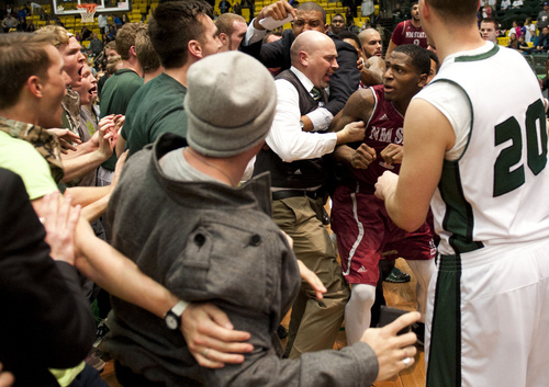 In this Thursday, Feb. 27, 2014 photo, New Mexico State's DK Eldridge, at right center in red and white uniform,  is controlled by security during a brawl involving players and fans who came onto the court when New Mexico State guard K.C. Ross-Miller hurled the ball at Utah Valley's Holton Hunsaker seconds after the Wolverines' 66-61 overtime victory against the Aggies.  (AP Photo/The Daily Herald, Grant Hindsley) MANDATORY CREDIT