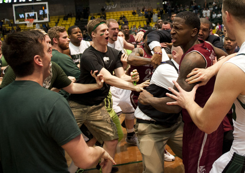 In this Thursday, Feb. 27, 2014 photo, New Mexico State's DK Eldridge, at right in red and white uniform, is held by security during  a brawl involving players and fans who came onto the court when New Mexico State guard K.C. Ross-Miller hurled the ball at Utah Valley's Holton Hunsaker seconds after the Wolverines' 66-61 overtime victory against the Aggies.  (AP Photo/The Daily Herald, Grant Hindsley) MANDATORY CREDIT