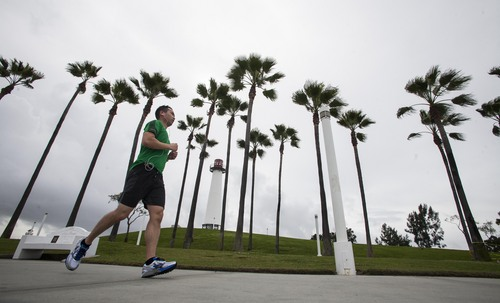 A man runs through Shoreline Aquatic Park in Long Beach, Calif. on Saturday, March 1, 2014. Earlier, a powerful Pacific storm hit the area, but did not put a major dent in a drought that is among the worst in recent California history. (AP Photo/Ringo H.W. Chiu)