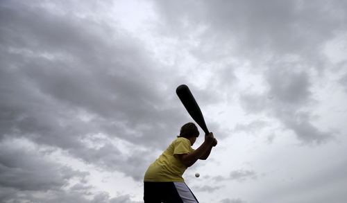 Oakland Athletics fan Shane Straw, of Sacramento, Calif., swings at a plastic ball under heavy clouds while waiting for the start of a spring training baseball game between the Athletics and the Texas Rangers Saturday, March 1, 2014, in Phoenix. Spring training games continued Saturday, as Arizona awaited more possible rainfall from a large storm that wreaked havoc on Southern California Friday. (AP Photo/Gregory Bull)