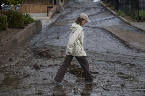 A woman walks over the mud and debris at the corner of Sierra Madre Avenue and Highcrest Road along the hillside in Glendora, Calif. on Saturday, March 1, 2014. A burst of heavy showers before dawn Saturday impacted wildfire-scarred mountainsides above foothill suburbs east of Los Angeles, causing another round of mud and debris flows in the city of Glendora. (AP Photo/Ringo H.W. Chiu)