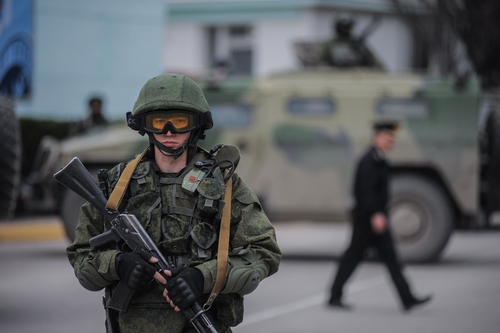 A gunman in unmarked uniform stands guard as troops take control the the Coast Guard offices in Balaklava on the outskirts of Sevastopol, Ukraine, Saturday, March 1, 2014. An emblem on one of the vehicles and their number plates identify them as belonging to the Russian military. Ukrainian officials have accused Russia of sending new troops into Crimea, a strategic Russia-speaking region that hosts a major Russian navy base.  (AP Photo/Andrew Lubimov)