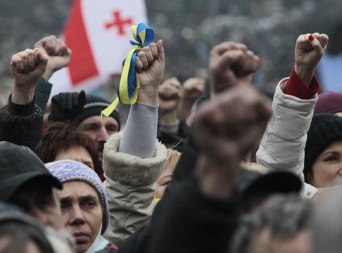 "People shout slogans and gesture,  during a rally in Kiev's Independence Square, Sunday, March 2, 2014. Ukraine's new prime minister urged Russian President Vladimir Putin to pull back his military Sunday in the conflict between the two countries, warning that ""we are on the brink of disaster."" The comments from Arseniy Yatsenyuk came as a convoy of Russian troops rolled toward Simferopol, the capital of Ukraine's Crimea region, a day after Russian forces took over the strategic Black Sea peninsula without firing a shot. (AP Photo/Sergei Chuzavkov)"