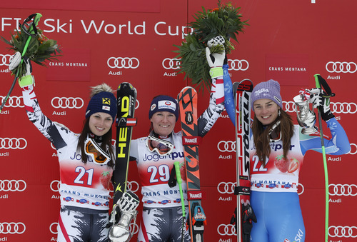 Austria's Andrea Fischbacher, center, winner of an alpine ski, World Cup women's downhill, celebrates on the podium with second-placed Anna Fenninger, also from Austria, left, and third-placed Tina Maze, from Slovenia, in Crans Montana, Switzerland, Sunday, March 2, 2014. (AP Photo/Marco Trovati)