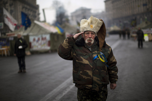 An anti-Yanukovych protester salutes as the Ukrainian national anthem is played at Kiev's Independence Square, Ukraine, Monday, March 3, 2014. The U.S. and its allies are weighing sanctions on Moscow and whether to bolster defenses in Europe in response to Russia's military advances on Ukraine. (AP Photo/Emilio Morenatti)