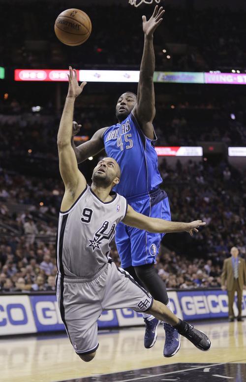 San Antonio Spurs' Tony Parker tries to make an off-balance shot as Dallas Mavericks' DeJuan Blair (45) defends during the first half of an NBA basketball game, Sunday, March 2, 2014, in San Antonio. (AP Photo/Eric Gay)