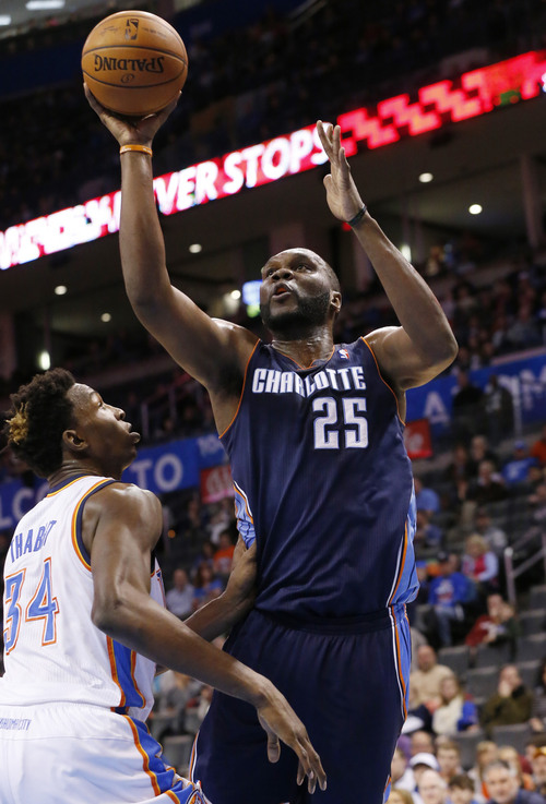 Charlotte Bobcats center Al Jefferson (25) shoots over Oklahoma City Thunder center Hasheem Thabeet (34) in the first quarter of an NBA basketball game in Oklahoma City, Sunday, March 2, 2014. (AP Photo/Sue Ogrocki)