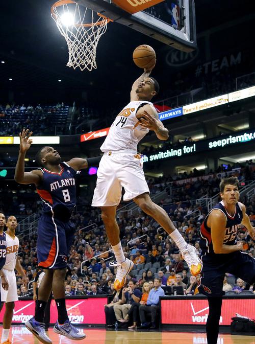Phoenix Suns' Gerald Green (14) dunks over Atlanta Hawks' Shelvin Mack (8) and Kyle Korver during the second half of an NBA basketball game, Sunday, March 2, 2014, in Phoenix. The Suns won 129-120. (AP Photo/Matt York)
