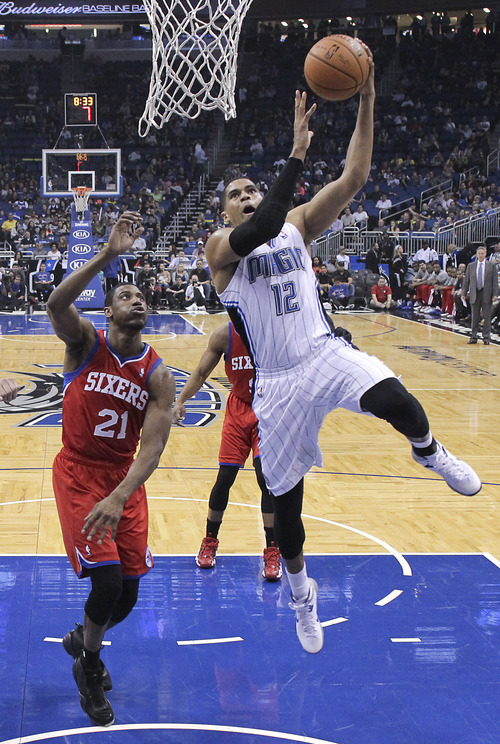 Orlando Magic's Tobias Harris (12) makes a basket as he gets past Philadelphia 76ers' Thaddeus Young (21) during the first half of an NBA basketball game in Orlando, Fla., Sunday, March 2, 2014. (AP Photo/John Raoux)