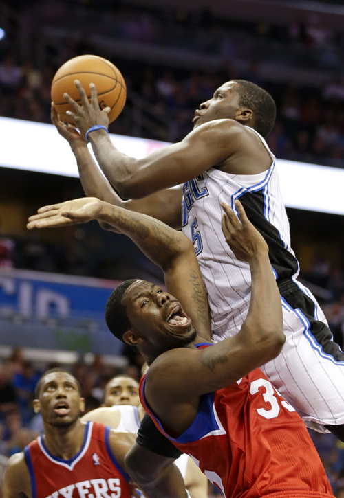 Orlando Magic's Victor Oladipo, right, is charged with an offensive foul as he collides with Philadelphia 76ers' Henry Sims during the second half of an NBA basketball game in Orlando, Fla., Sunday, March 2, 2014. Orlando won 92-81. (AP Photo/John Raoux)