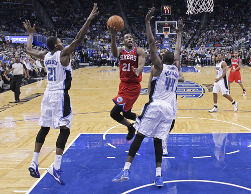 Philadelphia 76ers' Thaddeus Young, center, gets between Orlando Magic's Maurice Harkless, left, and Andrew Nicholson (44) for a shot during the second half of an NBA basketball game in Orlando, Fla., Sunday, March 2, 2014. Orlando won 92-81. (AP Photo/John Raoux)